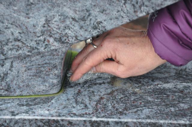 Mit leichtem Druck den Grabstein reinigen