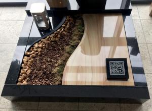 Moderne Urnengrab Platte aus schwarzem Granit und Iroko Quarzit. Der QR Code ist hier auf einem kleinen Sockel separat eingefräst und kann an verschiedenen Stellen auf der Grabanlage befestigt werden.