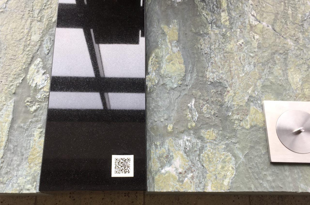 Modernes Urnengrab mit Grabplatte aus Dorfer Grün mit natürlich bearbeiteter Oberfläche und schwarzem Granit. Der QR Code wurde in einer Größe von 5x5 cm in die Grabplatte eingearbeitet.